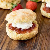 A Classic British Scone topped with strawberry jam and clotted cream