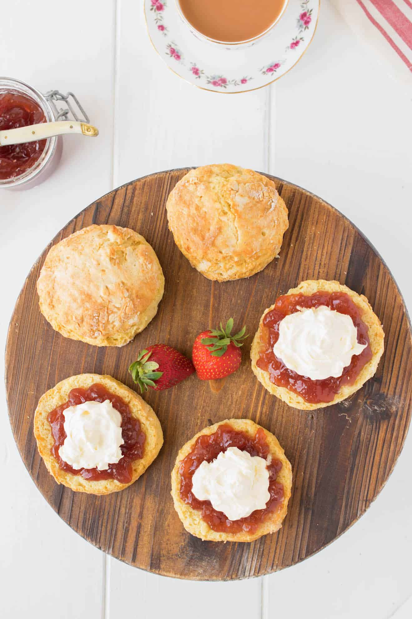 A round board of scones with jam and cream