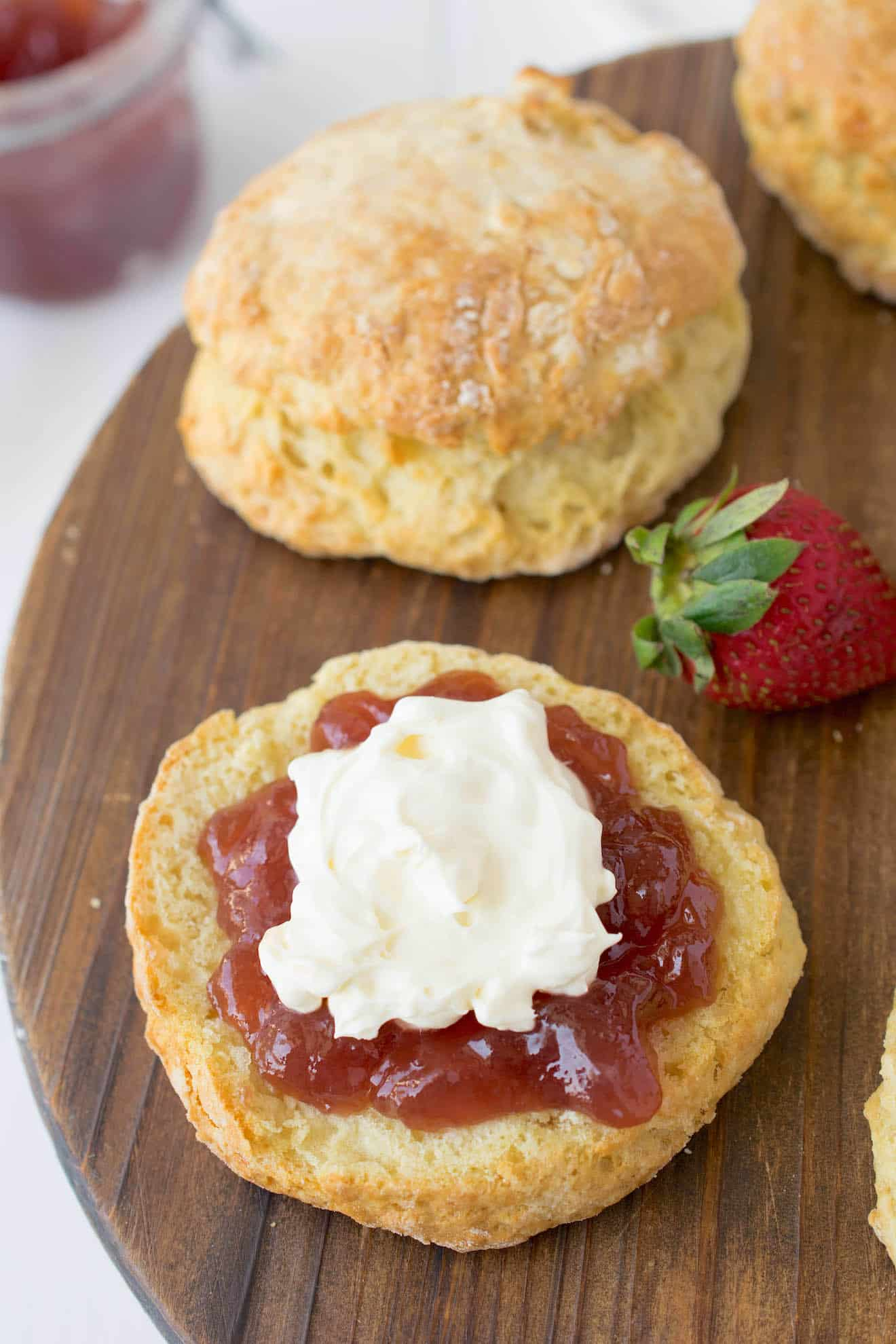 The bottom half of a scone topped with jam and clotted cream