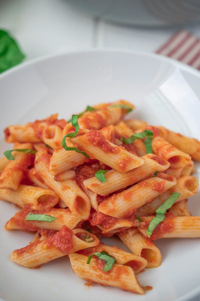 A closeup showing the tomato sauce on the pasta and fresh basil