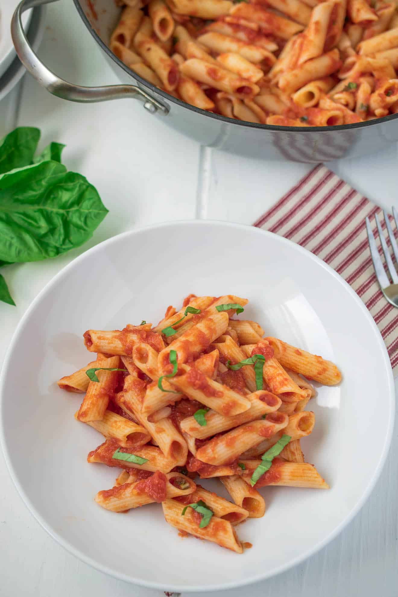 A bowl of classic penne all'arrabbiata with fresh basil and a pan it was cooked in