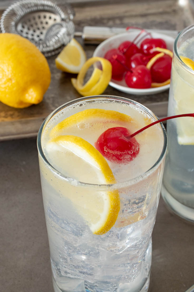 Lemon slices and red cherry in a glass of Tom Collins with lemons and cherries on a serving tray