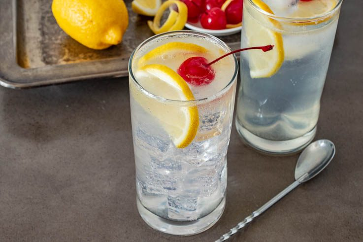 A tall glass filled with ice and Tom Collins garnished with lemon slices and a cherry