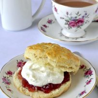 A scone cut in half topped with jam and clotted cream with a flower decorated china tea cup filled with tea