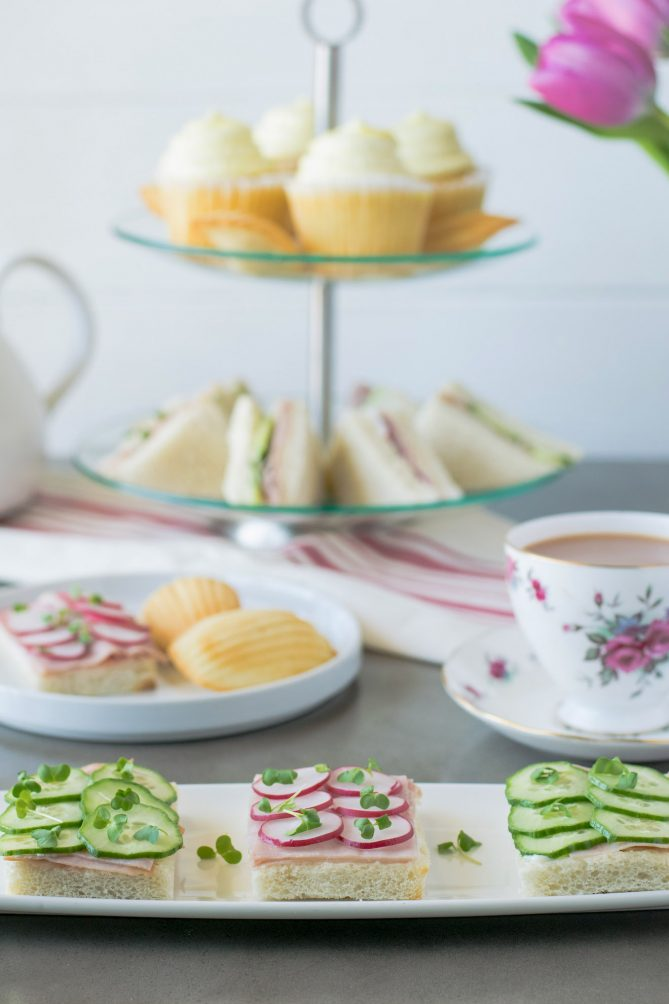A selection of cucumber and radish open face sandwiches with a cup of tea, a tiered cake stand with pastries and sandwiches