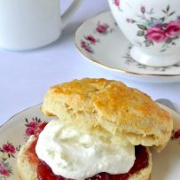 An English scone on a floured China plate spread with strawberry jam and clotted cream