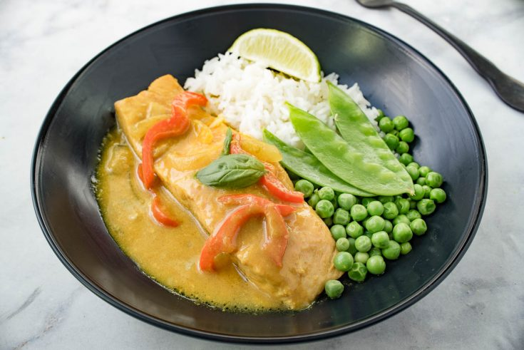 A filet of salmon bathed in coconut curry sauce with fresh peas, snow peas and white rice in a black bowl