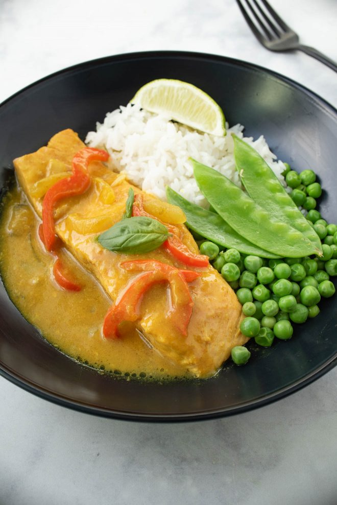A complete meal in a black bowl, salmon in curry sauce with peas, slow peas and white rice.
