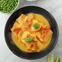 A view from above of 2 salmon filets in a bowl in curry sauce