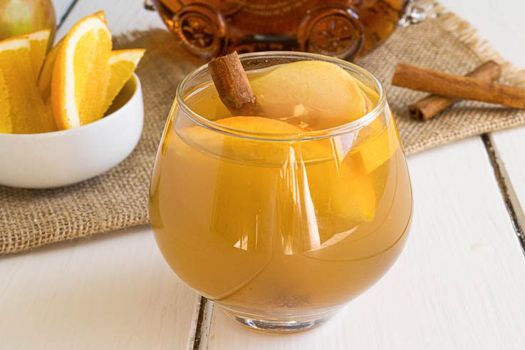 Cognac apple cider in a glass garnished with apple and orange slices and a cinnamon stick