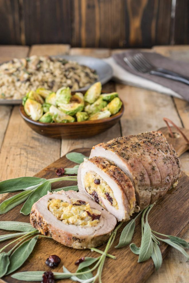 Cornbread apple cranberry stuffed pork loin sliced on a board with fresh sage