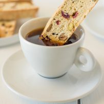 Dipping a cranberry orange pistachio biscotti into a cup of coffee