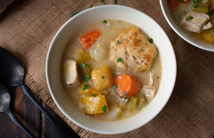 A bowl of creamy chicken stew with a sage and chive dumpling