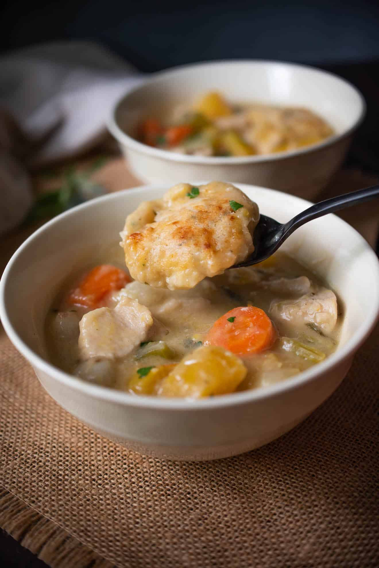 A dumpling on a spoon from Creamy Chicken Stew with Sage and Chive Dumplings