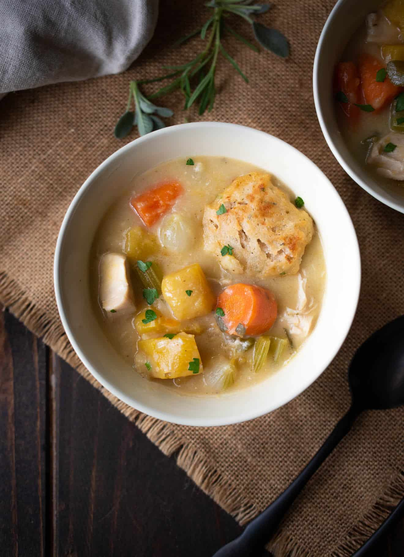 Creamy chicken stew with sage and chive dumplings in a bowl with a spoon