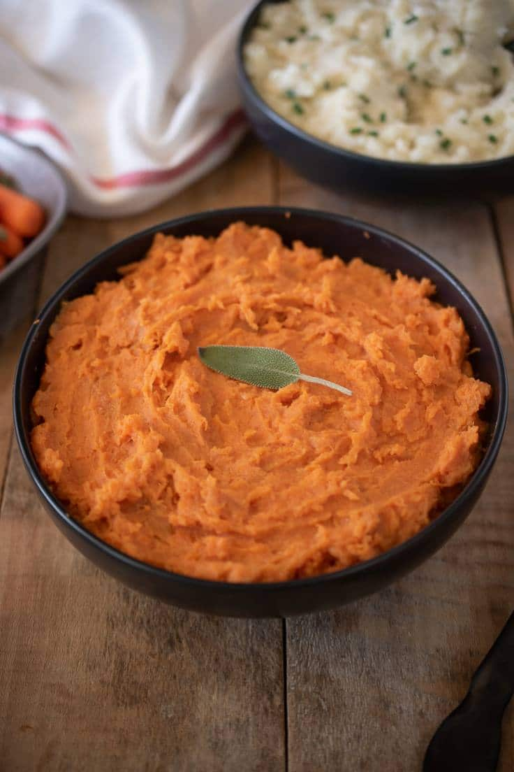 Mashed sweet potatoes in a black bowl garnished with a fresh sage leave