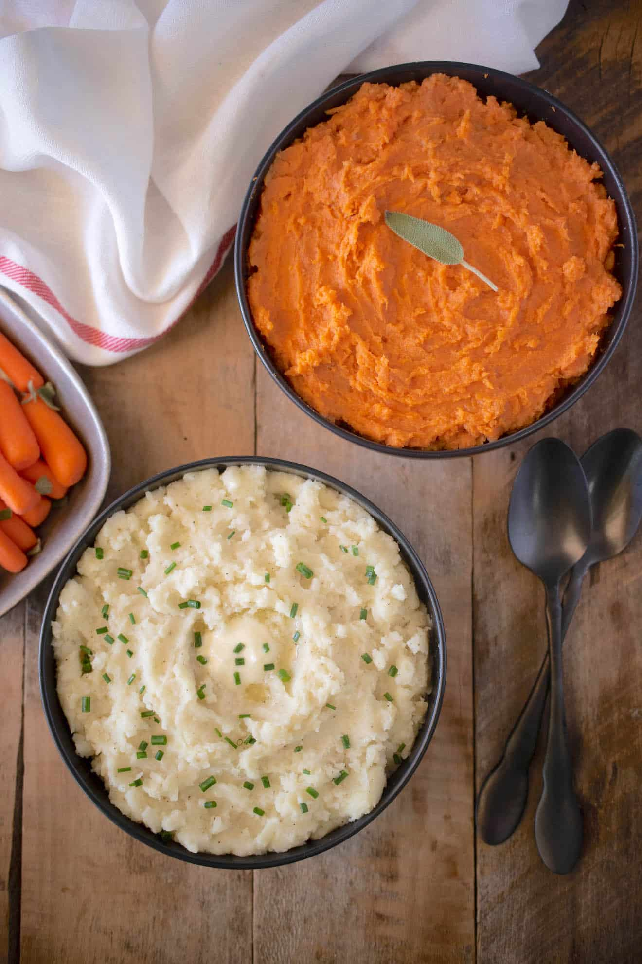 2 bowls of mashed potato, one with regular potatoes and one with yams/sweet potato