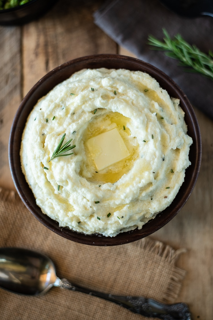 An overhead image of creamy rosemary cauliflower mash showing the butter melting in the center