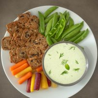 Tzatziki dipping sauce in a grey bowl on a white plate surrounded by vegetables and crackers.
