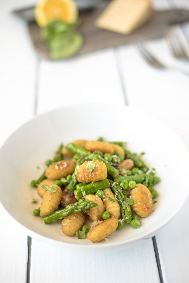 A white bowl filled with crispy gnocchi mixed with fresh asparagus and peas