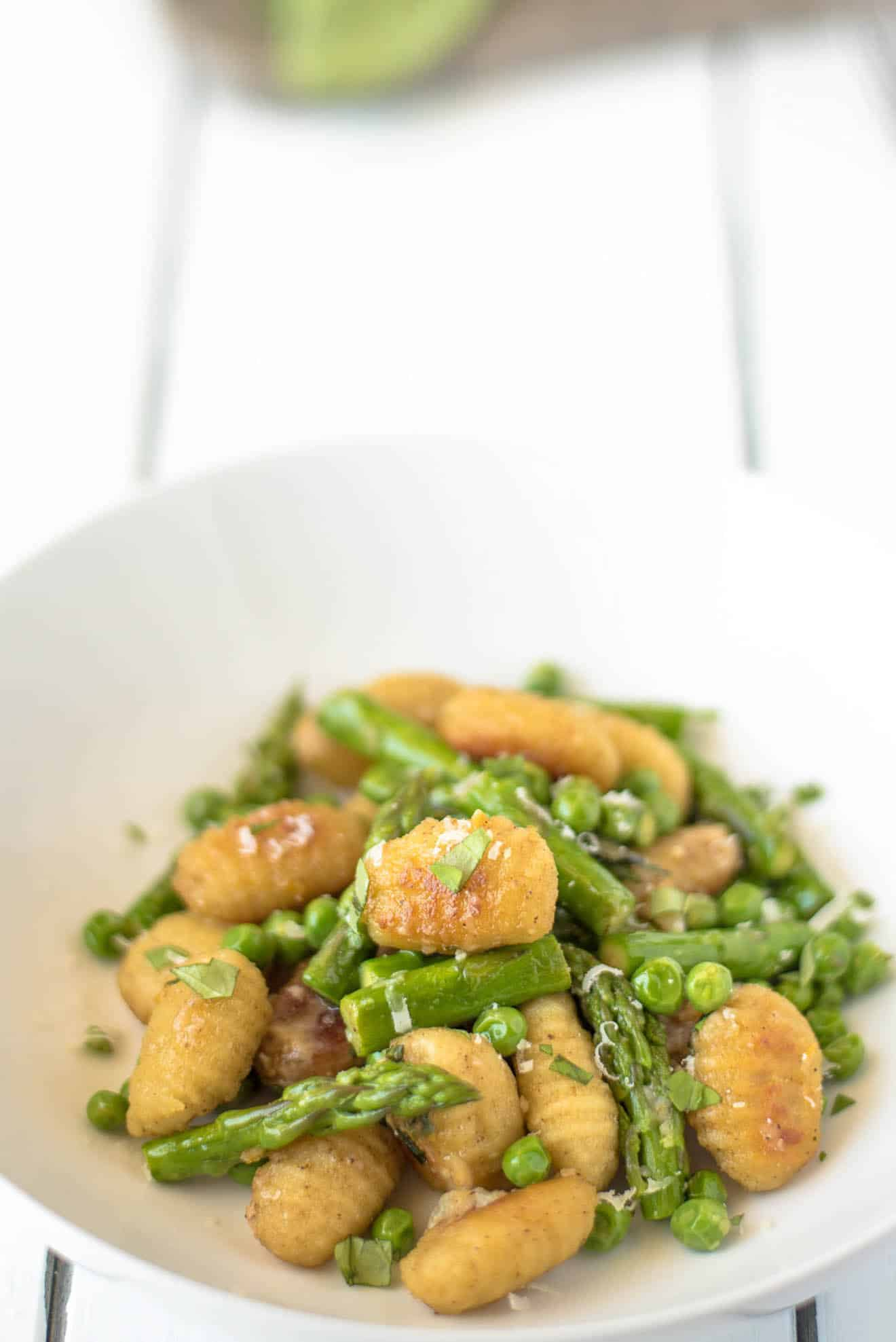 A closeup showing the brown and crispy gnocchi and vibrant green asparagus and peas