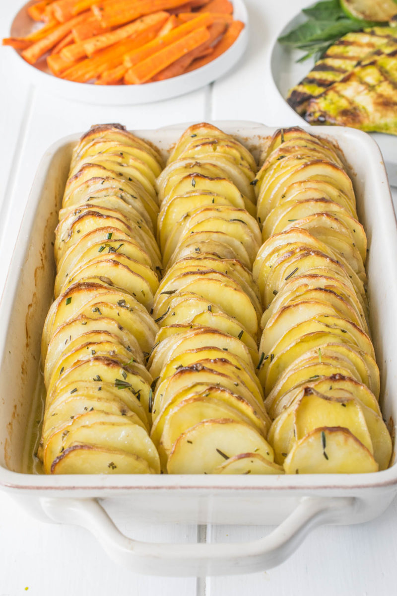 Crispy layered rosemary potatoes lined up in a baking dish fresh out of the oven