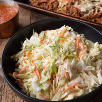 Crunchy vegetable coleslaw with vibrant orange carrot shreds and green scallions in a bowl