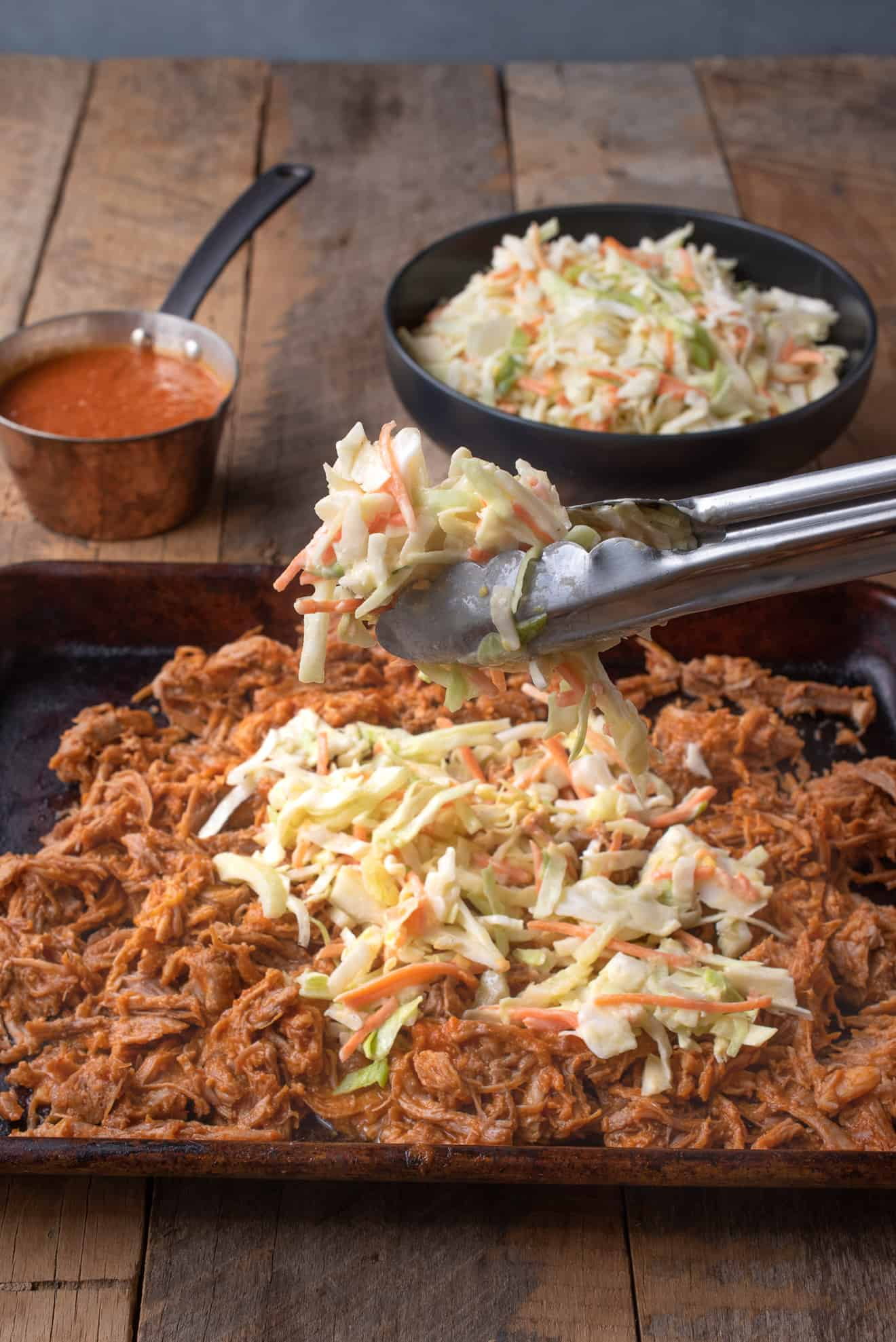 Topping a tray of pulled pork with crunch vegetable coleslaw