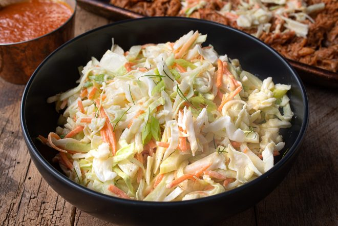 A black bowl filled with crunchy vegetable coleslaw