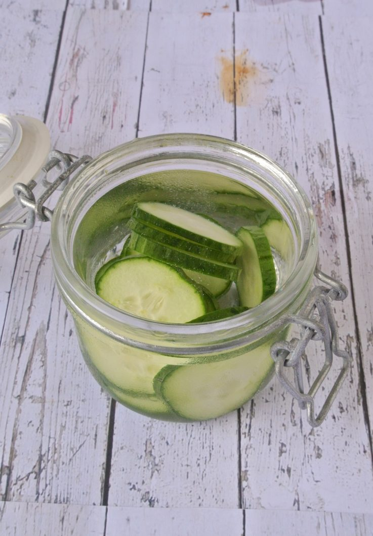 A jar of gin being infused with fresh cucumbers