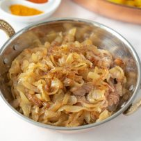 A copper bowl full of curry caramelized onions