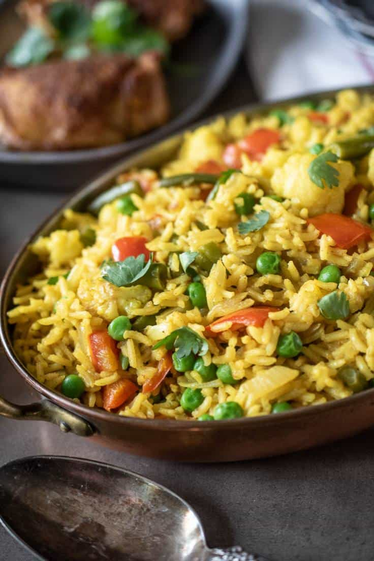 A closeup showing the beautiful yellow rice with the green peas and red peppers
