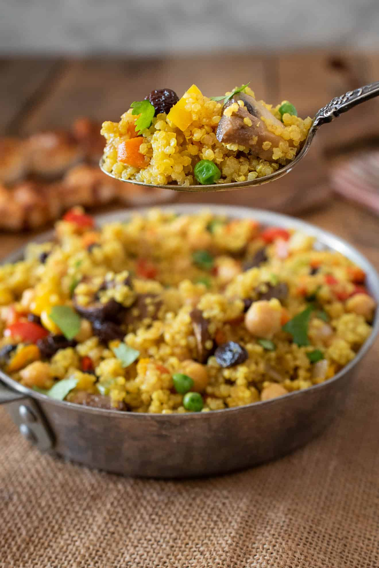 A spoonful of curry quinoa with mushrooms, peas, carrots and raisins
