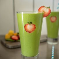 Detox green smoothie garnished with fresh strawberry slices