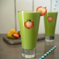 Strawberry slices on the inside of the glass and on the rim of this detox green smoothie