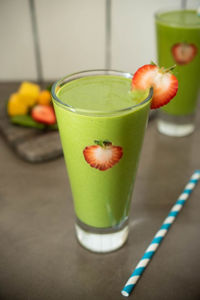 A glass of detox green smoothie with a straw and fresh strawberry slices