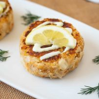 A white serving plate with crab cakes topped with lemon scallion sauce, lemon and fresh dill