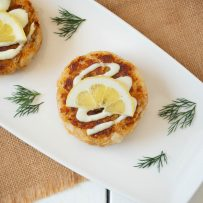 Crab cake viewed from overhead topped with sauce and a lemon slice