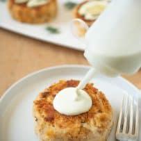 Squeezing lemon scallion sauce onto a crab cake