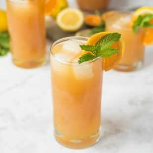 Earl Grey lemonade in a tall glass with fresh orange and mint