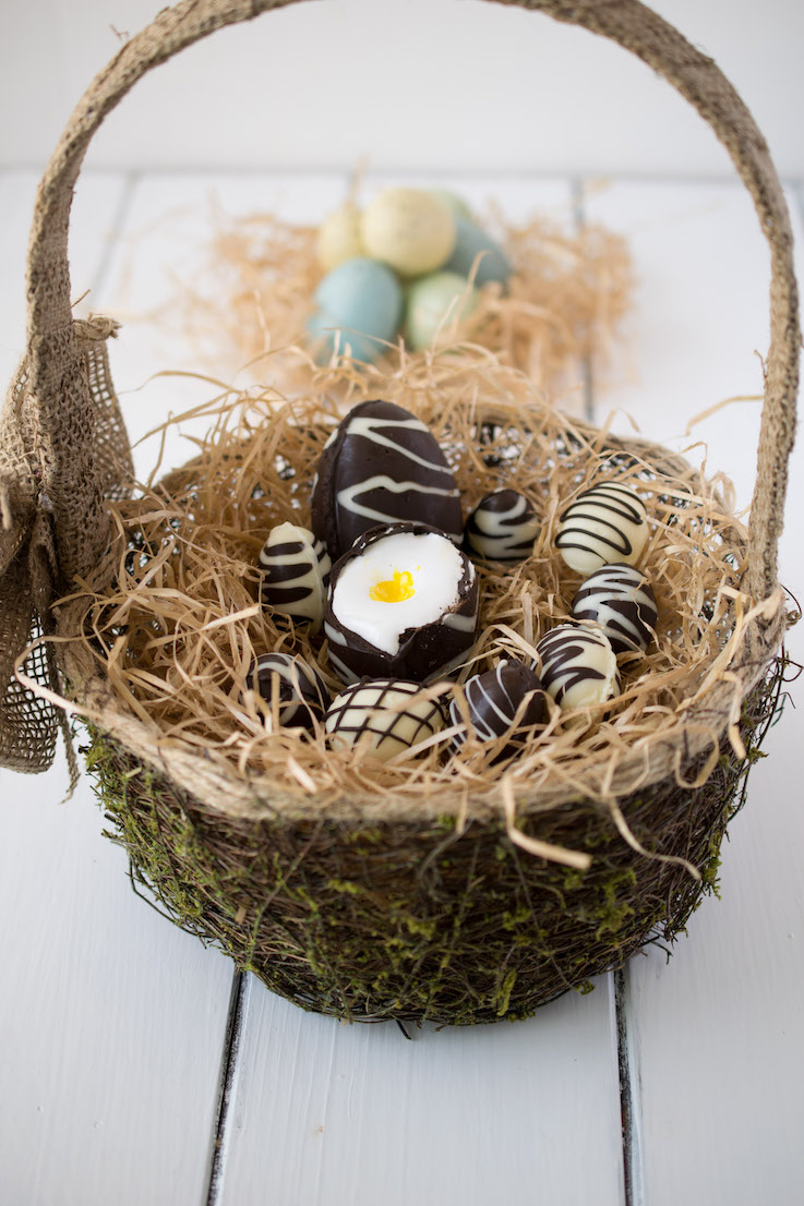 Chocolate creme eggs in an Easter basket filled with hay