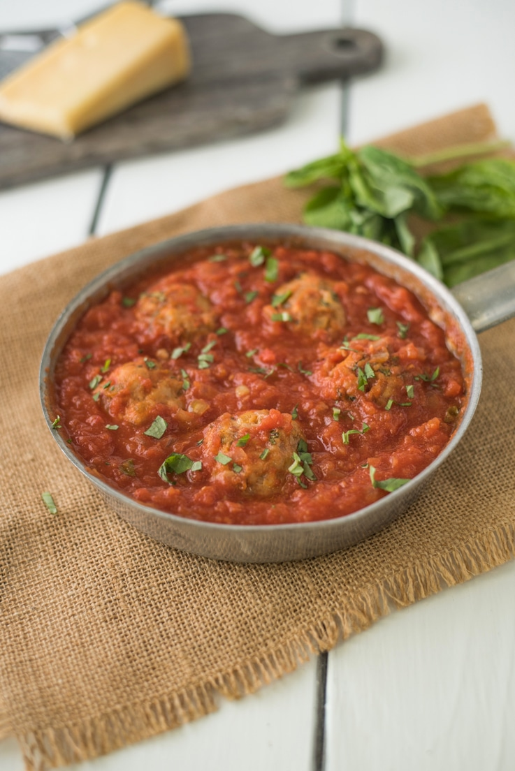 A pan of easy chicken meatballs in marinara sauce garnished with fresh basil