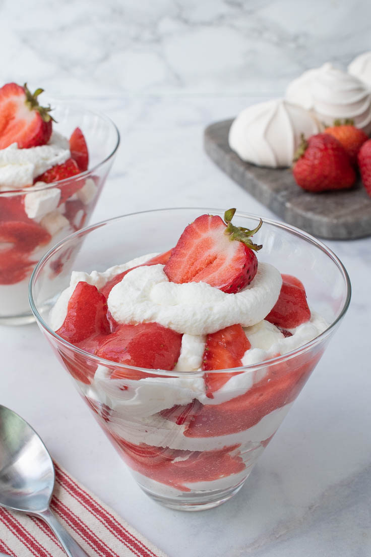 Layers of meringue, whipped cream and strawberries in a glass bowl