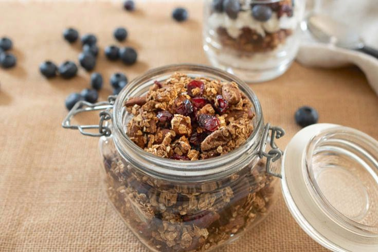 Easy Granola with Coconut Sugar in a jar with fresh blueberries