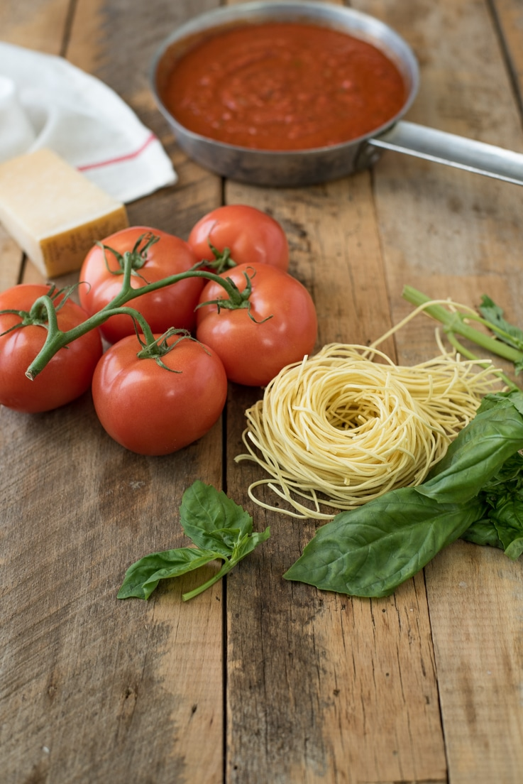 Fresh pasta rolled up with tomatoes on the vine, fresh basil, Parmesan and a pan of easy marinara sauce