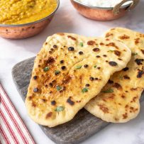 Browned naan bread garnished with cilantro