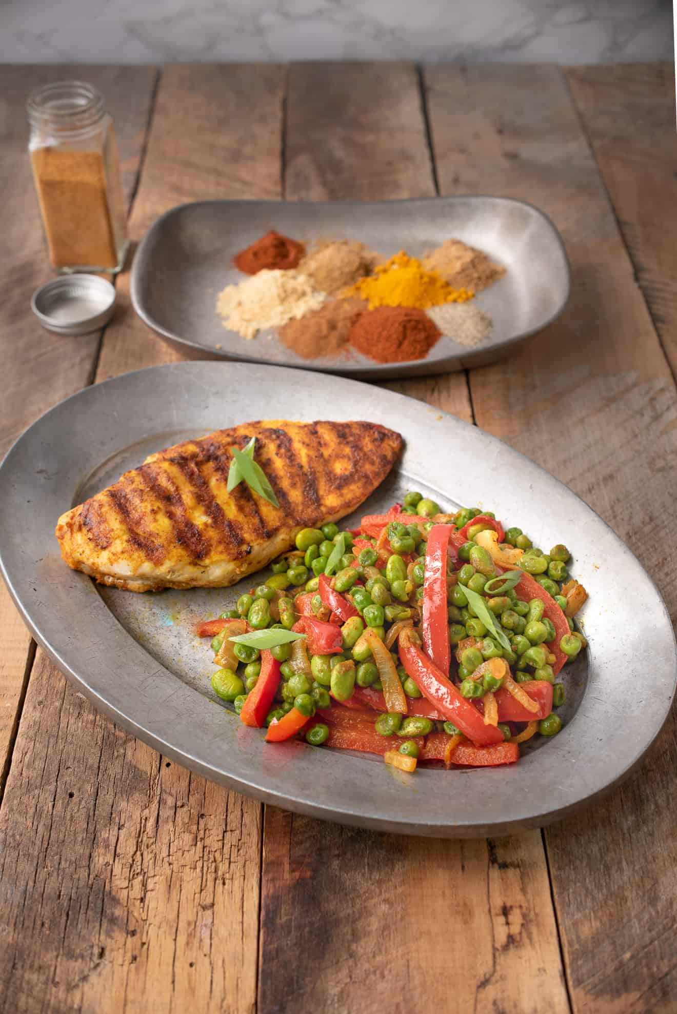 A oval plate with a grilled chicken breast with Indian spices peas