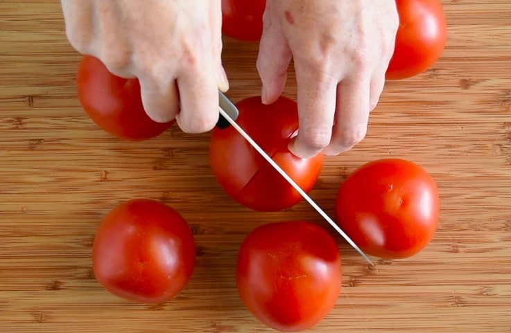The skin of fresh tomatoes is scored with an X