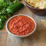 A bowl of Easy Restaurant-Style Red Salsa with cilantro and tortilla chips