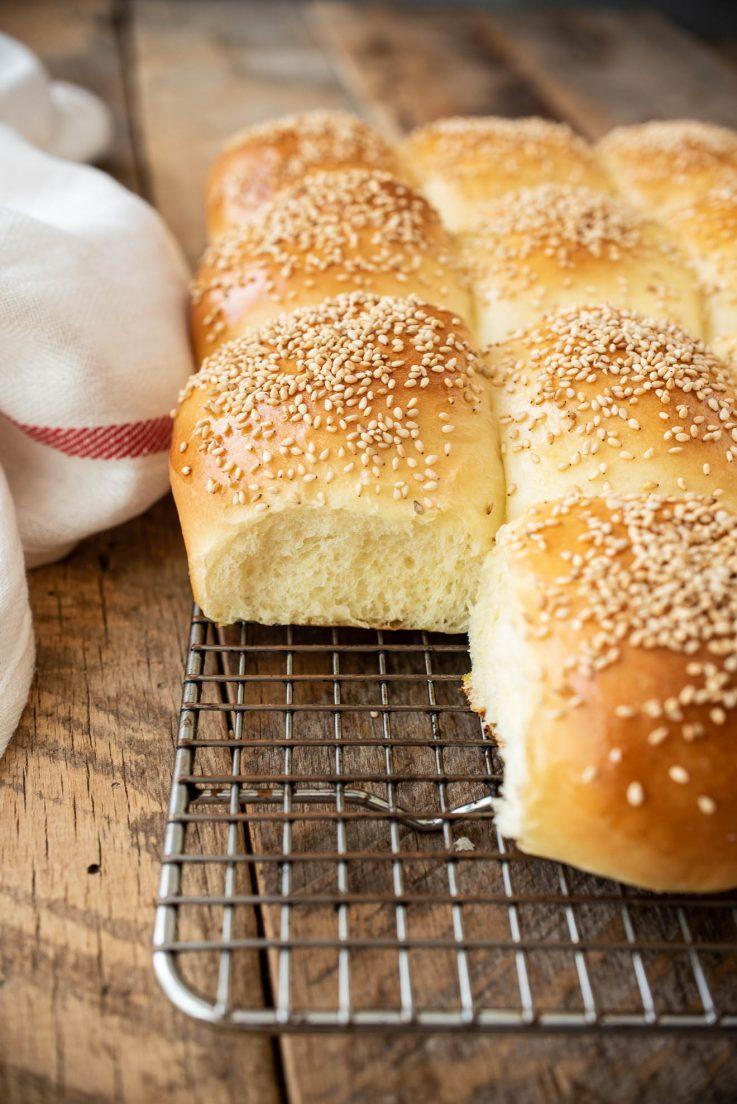 Sesame bread rolls on a cooling rack